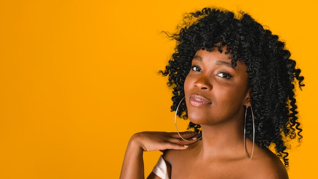 Mujer joven negra positiva en fondo brillante