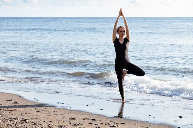 Mujer joven en negro haciendo yoga en la playa de arena