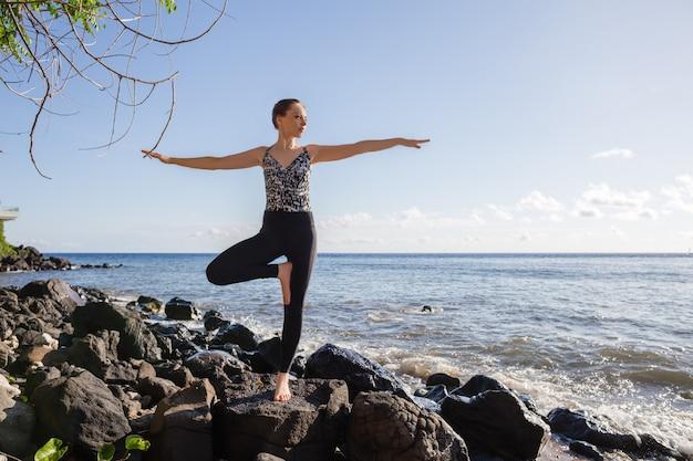 Mujer joven en negro haciendo yoga en la playa de roca