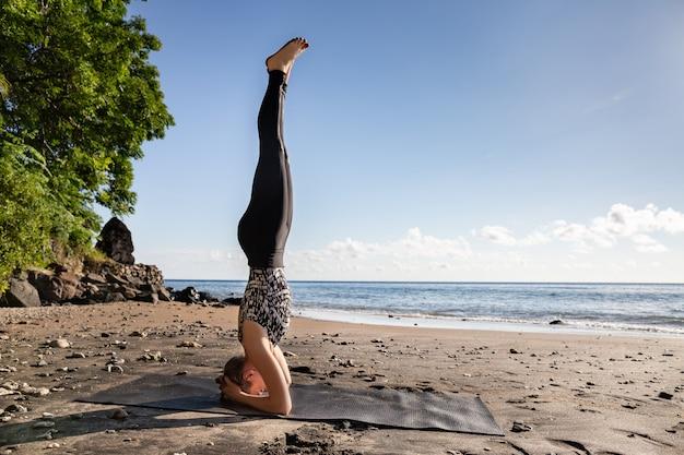 Mujer joven en el negro que hace su yoga en la playa asiática de la arena.