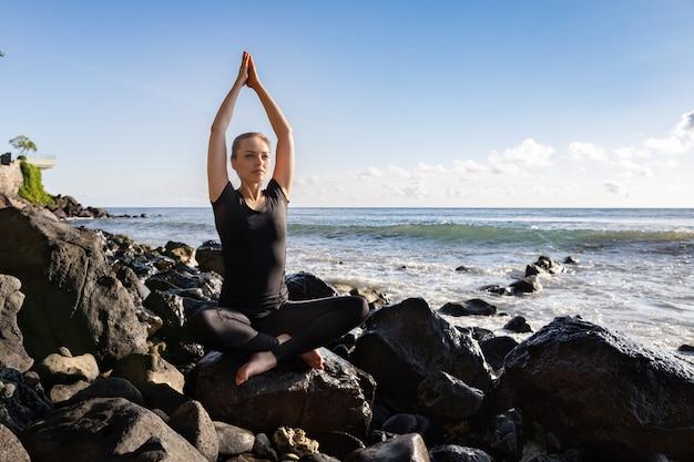 Mujer joven en negro que hace su yoga en la playa asiática de la roca