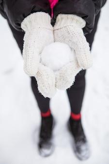 Mujer joven con nieve blanca suave natural en sus manos para hacer una bola de nieve, día de invierno en el bosque, al aire libre.