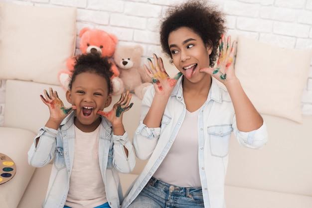 La mujer joven y la niña muestran las manos manchadas con pintura.