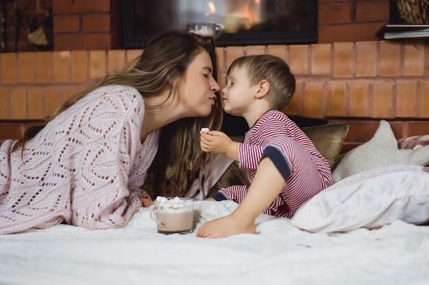 Mujer joven con un niño junto a la chimenea. madre e hijo beben cacao con marshmello cerca de la chimenea.