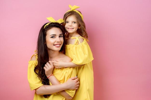 Mujer joven con niño lindo posando en vestidos amarillos