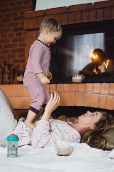 Mujer joven con un niño. mamá e hijo están jugando, divirtiéndose cerca de la chimenea.