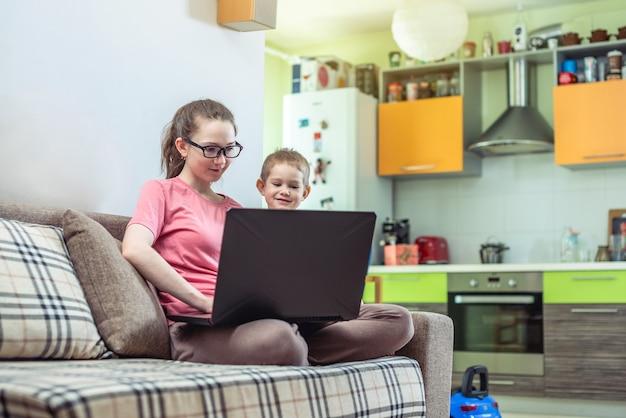 Una mujer joven con un niño pequeño de rodillas está sentada en una computadora portátil