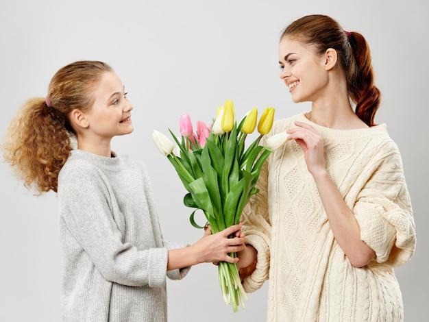 Mujer joven con un niño posando en el estudio con flores