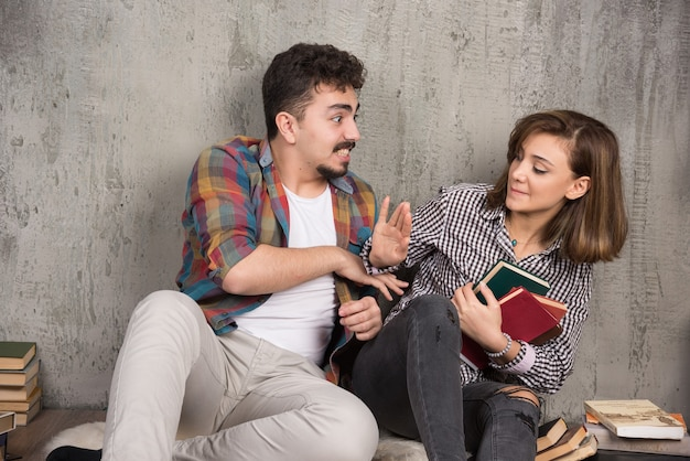 Mujer joven no le da libros al hombre