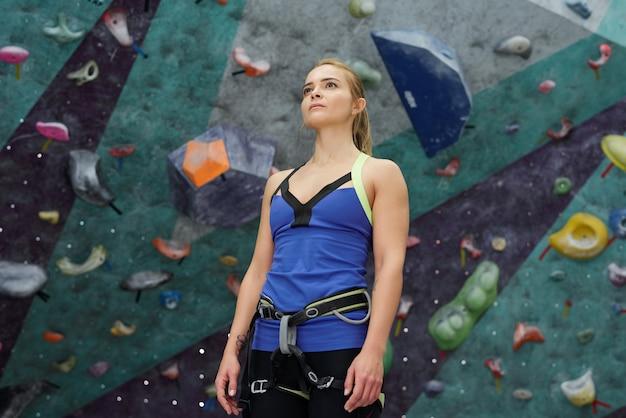 Mujer joven o instructor de escalada en ropa deportiva y cinturones de seguridad de pie con pequeñas rocas artificiales