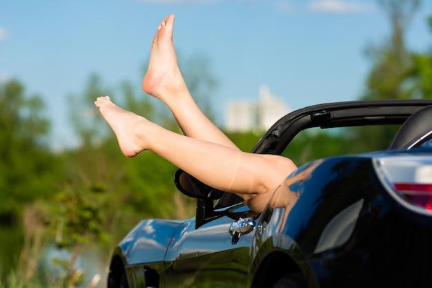 Mujer joven o sus piernas en un descapotable