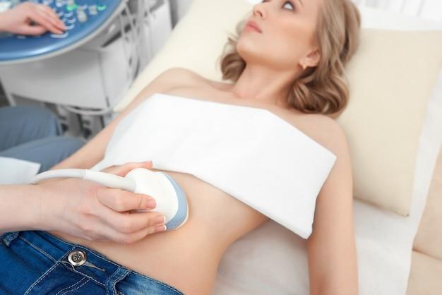 Mujer joven obteniendo un examen de ultrasonido en el hospi