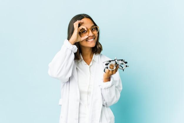 Mujer joven oculista sobre pared aislada emocionada manteniendo el gesto ok en el ojo