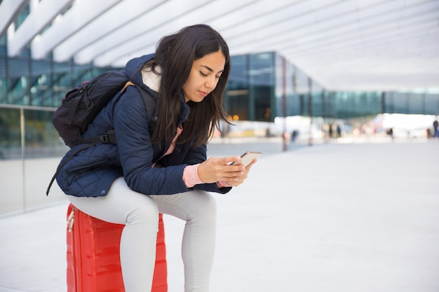 Mujer joven ocupada seria que usa smartphone en aeropuerto