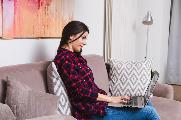 Mujer joven ocupada en usar la computadora portátil que se sienta en el sofá