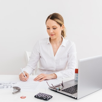 Mujer joven en la oficina que hace papeleo delante del ordenador portátil