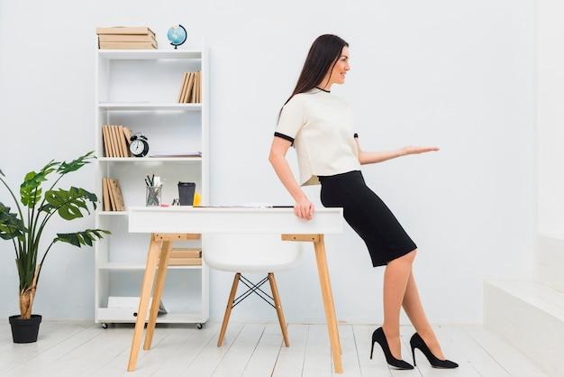 Mujer joven en la oficina sosteniendo algo en la palma