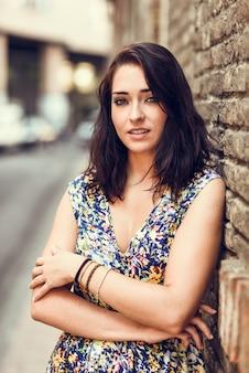 Mujer joven con ojos azules de pie junto a la pared de ladrillo