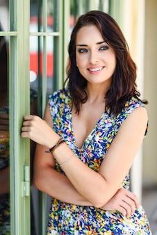 Mujer joven con los ojos azules que se colocan al lado de puerta hermosa.
