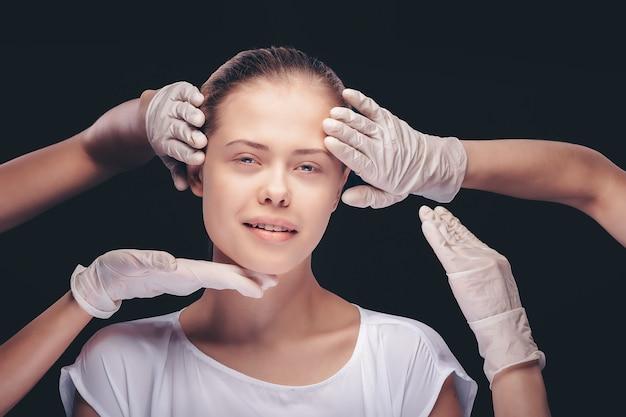 Mujer joven con los ojos cerrados tras un examen médico de la piel de su rostro por médicos de plástico