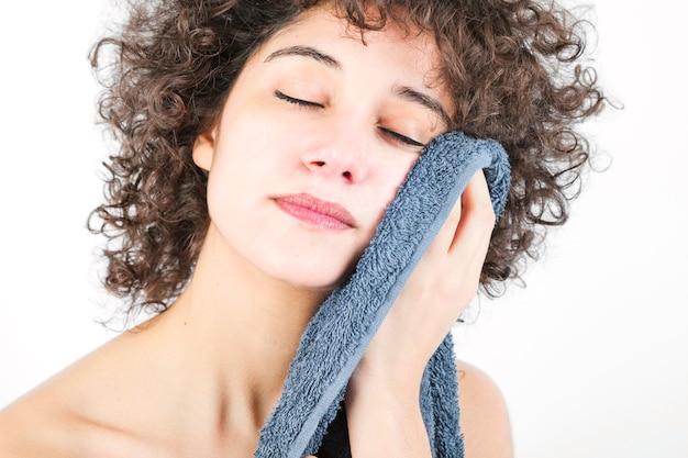 Mujer joven con los ojos cerrados limpiando el cuerpo con una toalla aislada sobre fondo blanco