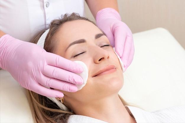 Mujer joven con los ojos cerrados recibiendo el procedimiento de limpieza facial en un salón de belleza