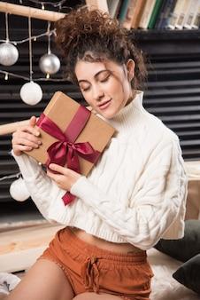 Una mujer joven con los ojos cerrados sosteniendo una caja de regalo con lazo