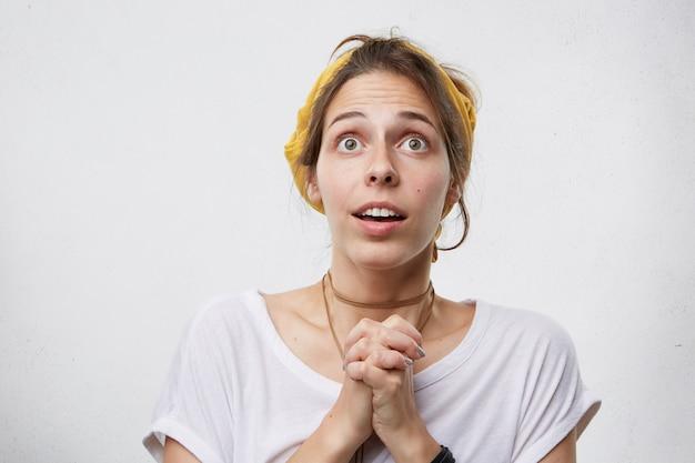 Mujer joven con ojos saltones llenos de esperanza mirando hacia arriba mientras reza manteniendo sus palmas juntas pidiendo a dios todo lo bueno. mujer confundida desconcertado rezando mientras está de pie contra la pared blanca