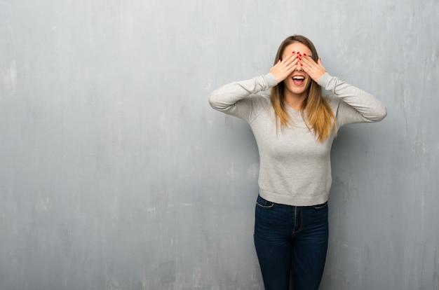 Mujer joven en ojos texturizados del recubrimiento de paredes por las manos. sorprendido de ver lo que viene por delante.