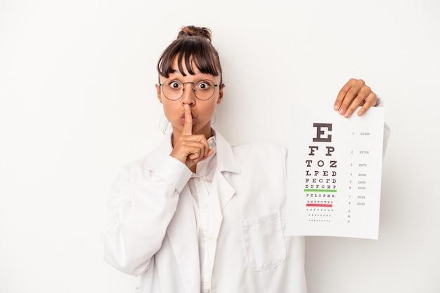 Mujer joven óptica de raza mixta haciendo una prueba aislada sobre fondo blanco manteniendo un secreto o pidiendo silencio.
