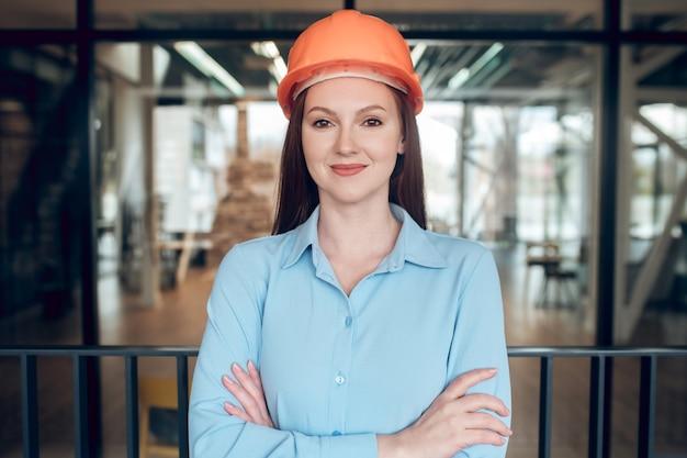 Mujer joven optimista en casco de seguridad