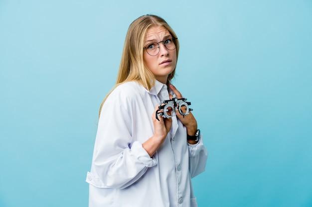 Mujer joven optometrista rusa en azul asustada y asustada.