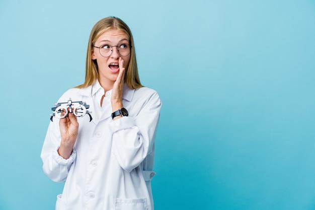 Mujer joven optometrista rusa en azul está diciendo una noticia secreta de frenado caliente y mirando a un lado