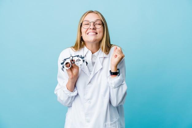 Mujer joven optometrista rusa en azul levantando el puño, sintiéndose feliz y exitosa. concepto de victoria.