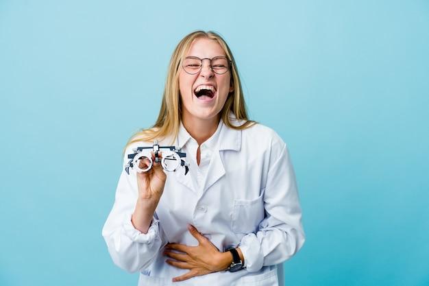Mujer joven optometrista rusa en azul se ríe felizmente y se divierte manteniendo las manos sobre el estómago.
