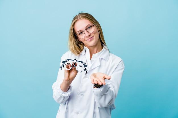 Mujer joven optometrista rusa en azul sosteniendo algo con las palmas