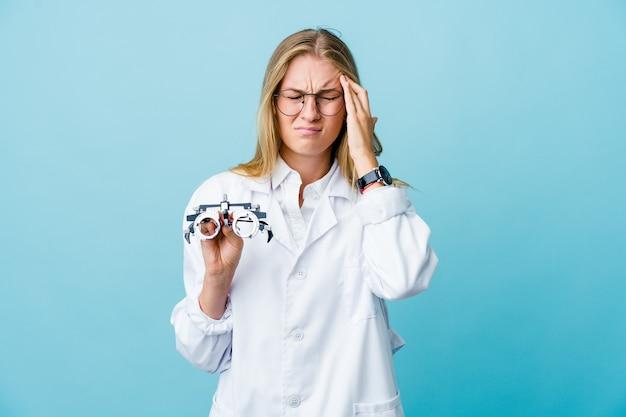 Mujer joven optometrista rusa en azul tocar templos y tener dolor de cabeza.