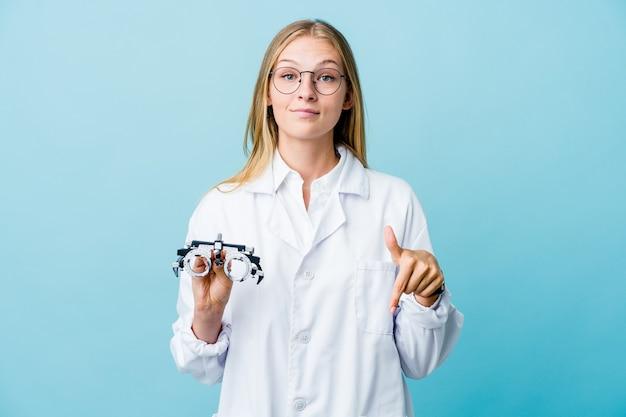 Mujer joven optometrista rusa en puntos azules hacia abajo con los dedos, sentimiento positivo.