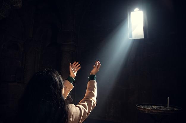 Mujer joven de oración a la luz de la iglesia.