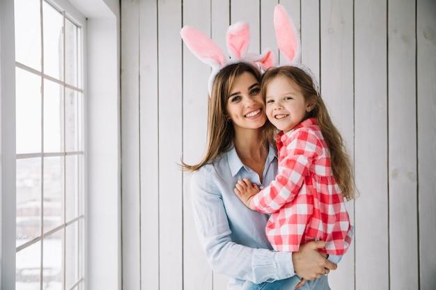 Mujer joven en orejas de conejo con hija en brazos