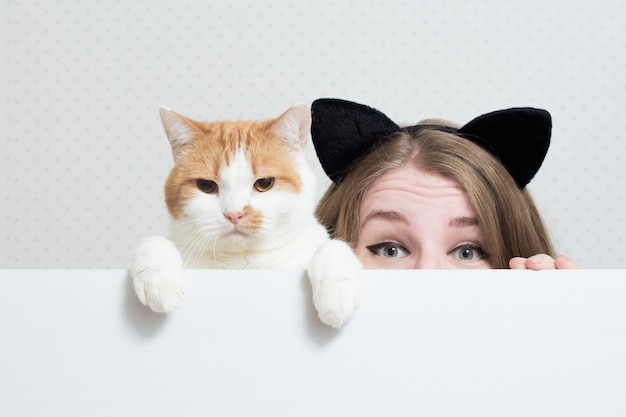 Mujer joven con orejas de gato en la cabeza y el gato se esconden detrás de una pancarta blanca.