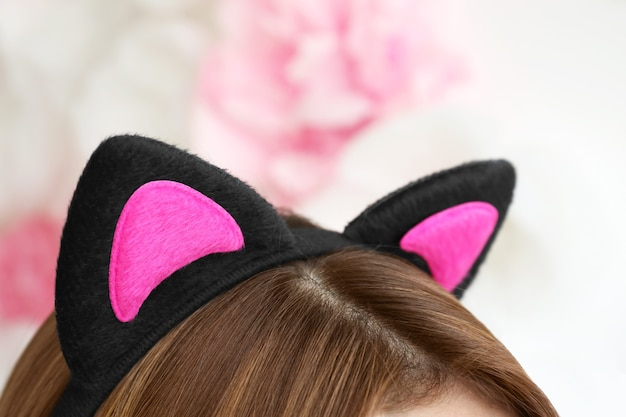 Mujer joven, en, orejas de gato, en, fondo borroso, primer plano