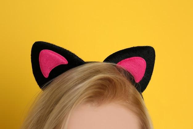 Mujer joven en orejas de gato sobre fondo de color, primer plano