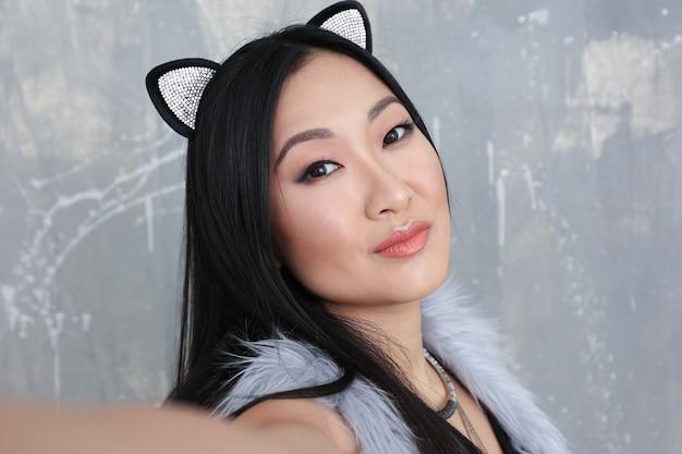 Mujer joven en orejas de gato sobre fondo de color