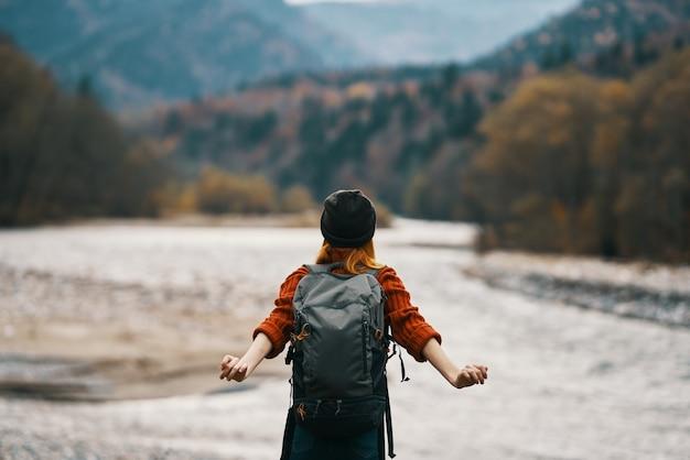 Mujer joven en la orilla del río con viaje de modelo de turismo de mochila