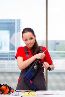 Mujer joven en overoles haciendo reparaciones