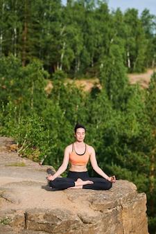 Mujer joven pacífica con los ojos cerrados sentado con las piernas cruzadas en las montañas y practicando la meditación en silencio