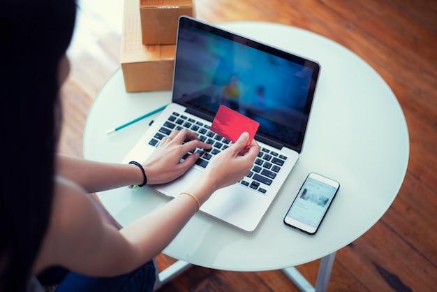 Mujer joven pagando compras en línea con una tarjeta de crédito en casa