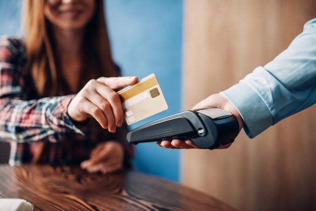 Mujer joven pagando con tarjeta de crédito en el café