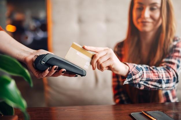 Mujer joven pagar por teléfono móvil en la cafetería